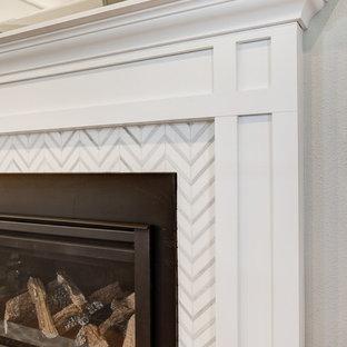 デンバーの大きいミッドセンチュリースタイルのおしゃれなLDK (グレーの壁、無垢フローリング、標準型暖炉、石材の暖炉まわり、壁掛け型テレビ、茶色い床) の写真