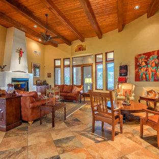 アルバカーキの中くらいのサンタフェスタイルのおしゃれなLDK (マルチカラーの壁、スレートの床、標準型暖炉、漆喰の暖炉まわり、テレビなし、マルチカラーの床) の写真
