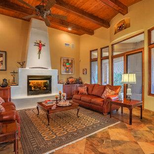 アルバカーキの中サイズのサンタフェスタイルのおしゃれなLDK (マルチカラーの壁、スレートの床、標準型暖炉、漆喰の暖炉まわり、テレビなし、マルチカラーの床) の写真