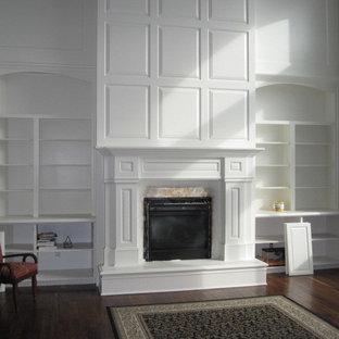 ソルトレイクシティの大きいトラディショナルスタイルのおしゃれなLDK (フォーマル、グレーの壁、濃色無垢フローリング、吊り下げ式暖炉、漆喰の暖炉まわり、テレビなし、茶色い床) の写真
