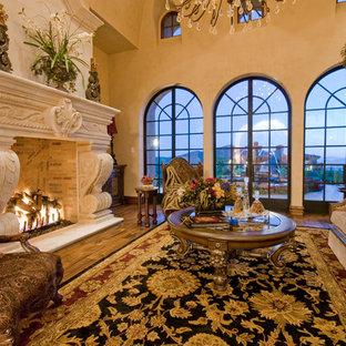 フェニックスの巨大な地中海スタイルのおしゃれなLDK (フォーマル、ベージュの壁、濃色無垢フローリング、標準型暖炉、石材の暖炉まわり、テレビなし、茶色い床) の写真