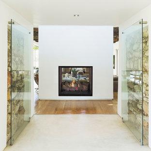 Foto di un soggiorno classico con pareti bianche e camino bifacciale