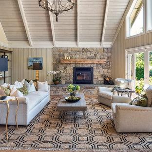Foto di un soggiorno country chiuso con pareti gialle, pavimento in legno massello medio, camino classico, cornice del camino in metallo e pavimento marrone