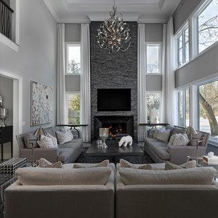 Inspiration pour un très grand salon traditionnel ouvert avec un mur gris, un sol en bois brun, une cheminée standard, un manteau de cheminée en pierre et un téléviseur fixé au mur.