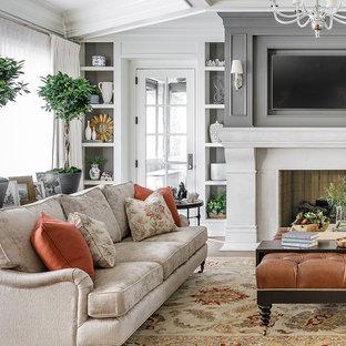 Foto di un grande soggiorno tradizionale aperto con pareti grigie, pavimento in legno massello medio, camino classico, TV a parete e pavimento marrone