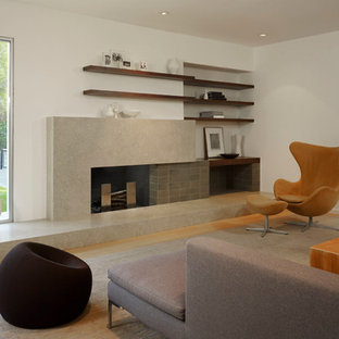 This is an example of a large modern formal open concept living room in San Francisco with white walls, light hardwood floors, a standard fireplace, a concrete fireplace surround and no tv.