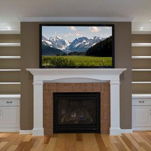 Diseño de salón abierto, tradicional, de tamaño medio, con paredes marrones, suelo de madera clara, chimenea tradicional, marco de chimenea de ladrillo y televisor colgado en la pared