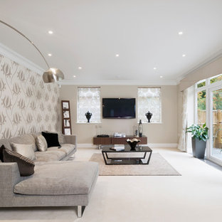 Design ideas for a medium sized contemporary living room in Buckinghamshire with beige walls, carpet, a wall mounted tv, beige floors and no fireplace.