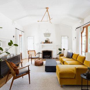 ロサンゼルスの中サイズの地中海スタイルのおしゃれなLDK (白い壁、無垢フローリング、標準型暖炉、漆喰の暖炉まわり、テレビなし、茶色い床) の写真