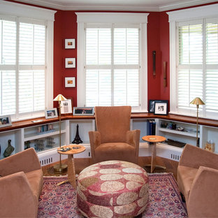 Example of a mid-sized classic dark wood floor living room library design in Boston with red walls, no fireplace and no tv