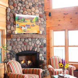 Exemple d'un salon montagne avec une cheminée d'angle et un manteau de cheminée en pierre.