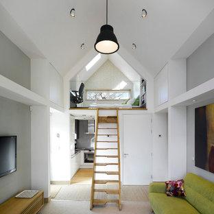 Imagen de salón contemporáneo, pequeño, con paredes grises y televisor colgado en la pared