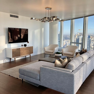 Example of a trendy dark wood floor and brown floor living room design in San Diego with white walls and a wall-mounted tv