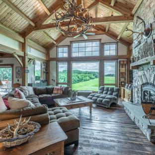 ミルウォーキーの大きいラスティックスタイルのおしゃれなLDK (ベージュの壁、濃色無垢フローリング、標準型暖炉、石材の暖炉まわり、埋込式メディアウォール、茶色い床) の写真