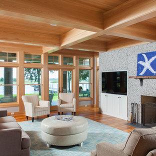他の地域の中サイズのビーチスタイルのおしゃれなLDK (グレーの壁、淡色無垢フローリング、標準型暖炉、コンクリートの暖炉まわり、埋込式メディアウォール、オレンジの床) の写真