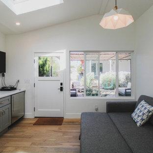 Inspiration för små klassiska separata vardagsrum, med vita väggar, laminatgolv, en väggmonterad TV och brunt golv