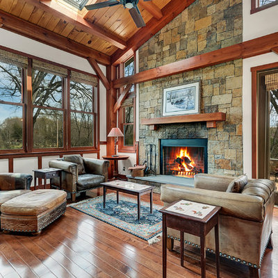 Example of a mid-sized mountain style open concept and formal brown floor and dark wood floor living room design in DC Metro with a stone fireplace, white walls and a standard fireplace