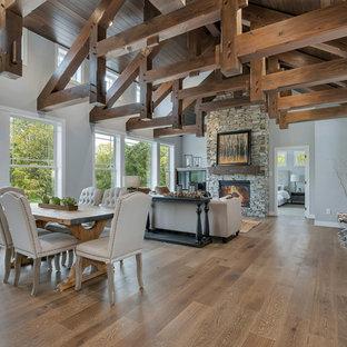 Modelo de salón abierto, de estilo de casa de campo, de tamaño medio, con paredes grises, suelo de madera en tonos medios, chimenea tradicional, marco de chimenea de piedra y suelo marrón