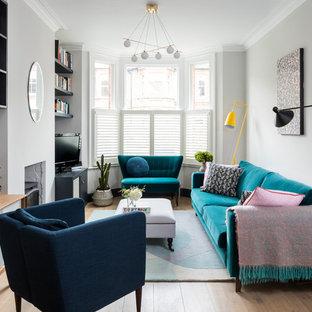 Foto på ett vintage separat vardagsrum, med grå väggar, mellanmörkt trägolv, en standard öppen spis, en fristående TV och brunt golv