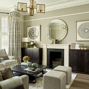 Design ideas for a small classic formal living room in London with medium hardwood flooring, a standard fireplace, a stone fireplace surround, a concealed tv, grey walls and brown floors.