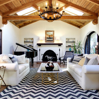 Example of a mountain style medium tone wood floor living room design in Los Angeles with white walls, a standard fireplace and a brick fireplace