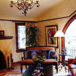 サンフランシスコの中サイズのヴィクトリアン調のおしゃれな独立型リビング (フォーマル、ベージュの壁、無垢フローリング、標準型暖炉、漆喰の暖炉まわり、テレビなし、ベージュの床) の写真