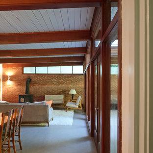 Ejemplo de salón abierto, retro, de tamaño medio, con paredes blancas, estufa de leña, suelo de linóleo y marco de chimenea de ladrillo