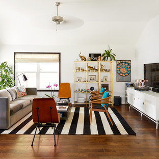 Living room - large eclectic open concept brown floor and dark wood floor living room idea in Austin with white walls and a wall-mounted tv