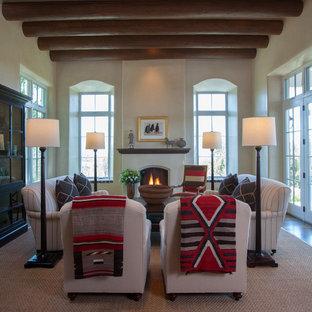Esempio di un soggiorno stile americano aperto con sala formale, pareti beige, parquet scuro, camino classico, cornice del camino in pietra e nessuna TV