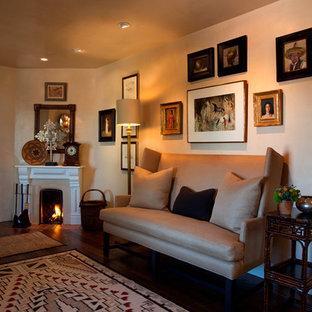 アルバカーキの広いサンタフェスタイルのおしゃれな独立型リビング (ベージュの壁、濃色無垢フローリング、コーナー設置型暖炉、木材の暖炉まわり、テレビなし) の写真