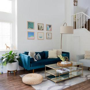 Imagen de salón para visitas cerrado, bohemio, pequeño, sin chimenea, con paredes blancas, suelo de madera oscura y televisor colgado en la pared