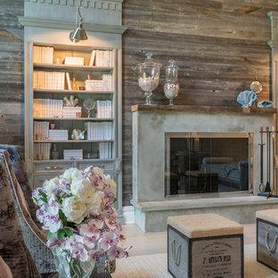 Bild på ett stort lantligt allrum med öppen planlösning, med ett bibliotek, grå väggar, ljust trägolv, en standard öppen spis och en spiselkrans i betong