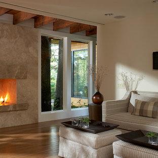 ニューヨークの広いコンテンポラリースタイルのおしゃれな独立型リビング (フォーマル、ベージュの壁、竹フローリング、標準型暖炉、石材の暖炉まわり、テレビなし) の写真