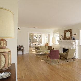 Idee per un soggiorno stile americano di medie dimensioni e aperto con pareti bianche, parquet chiaro, camino classico e cornice del camino in cemento