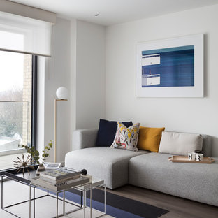 Inspiration for a contemporary living room in London with white walls and brown floors.