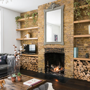 Design ideas for a large mediterranean open plan living room in London with dark hardwood flooring, white walls, a standard fireplace, a brick fireplace surround, a freestanding tv and brown floors.