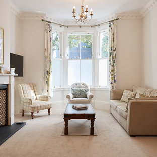 Inspiration for a medium sized classic formal enclosed living room in London with white walls, carpet, a standard fireplace, a metal fireplace surround, a wall mounted tv and beige floors.