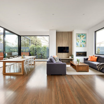 Example of a trendy formal and open concept medium tone wood floor living room design in Melbourne with white walls, a ribbon fireplace and a wall-mounted tv