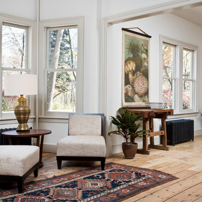 Ornate medium tone wood floor and brown floor living room photo in New York with white walls