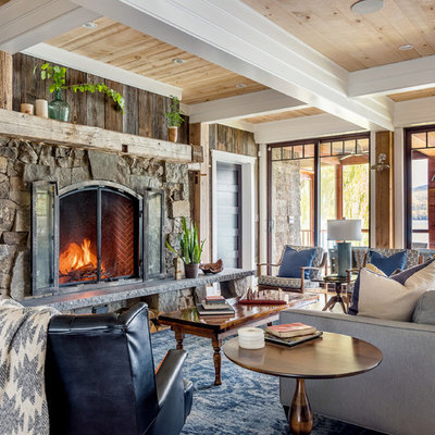 Inspiration for a large rustic open concept beige floor and medium tone wood floor living room remodel in New York with brown walls, a standard fireplace, a stone fireplace and no tv
