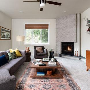 Immagine di un soggiorno contemporaneo di medie dimensioni e aperto con pareti bianche, moquette, camino ad angolo, cornice del camino piastrellata, TV a parete e pavimento grigio