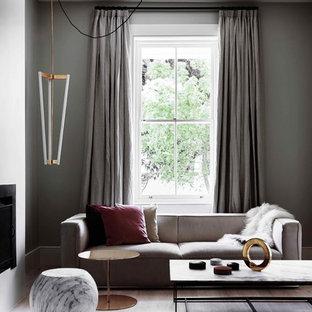 Modelo de salón abierto, actual, de tamaño medio, con paredes grises, suelo de madera clara y chimenea tradicional