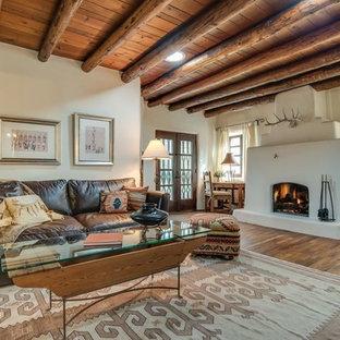 アルバカーキの中サイズのサンタフェスタイルのおしゃれなLDK (ベージュの壁、淡色無垢フローリング、標準型暖炉、コンクリートの暖炉まわり、フォーマル、テレビなし、茶色い床) の写真