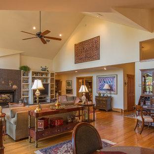 他の地域の中サイズのトラディショナルスタイルのおしゃれなリビング (ベージュの壁、竹フローリング、石材の暖炉まわり、埋込式メディアウォール) の写真