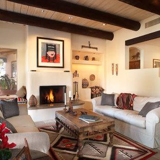 Exemple d'un salon sud-ouest américain avec un mur blanc et une cheminée standard.