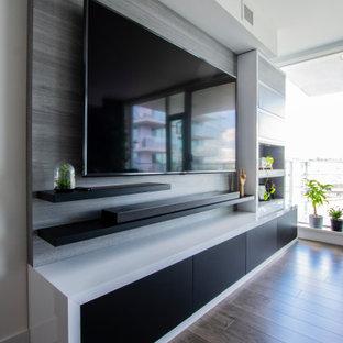 Inspiration för ett litet funkis loftrum, med grå väggar, mörkt trägolv, en inbyggd mediavägg och brunt golv