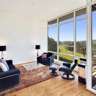 Foto di un grande soggiorno moderno aperto con pareti bianche, parquet chiaro, nessun camino, TV a parete e pavimento giallo