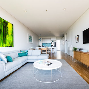 Inspiration for a small contemporary open concept living room in Adelaide with white walls, a wall-mounted tv, medium hardwood floors and brown floor.