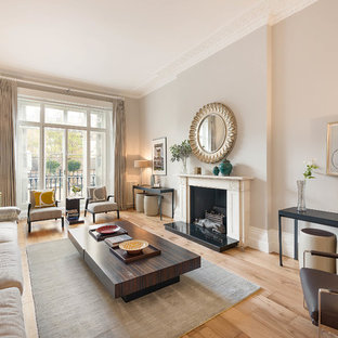 Photo of a classic formal living room in London with grey walls, light hardwood flooring, a standard fireplace, no tv and beige floors.