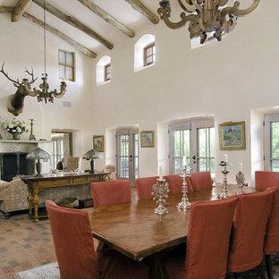 Стильный дизайн: огромная парадная, открытая гостиная комната в стиле фьюжн с белыми стенами, кирпичным полом, стандартным камином и фасадом камина из камня без ТВ - последний тренд